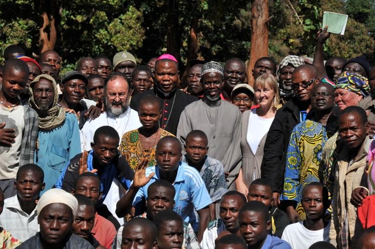 Uskup Agung Bangui Dieudonne Nzapalainga (belakang, tengah, kiri) dan presiden dari komunitas Muslim Afrika Tengah, Imam Omar Rabine Layama (belakang, tengah, kanan), berpose dengan anggota komunitas Kristen dan Muslim setelah pertemuan konsiliasi mengakhiri seminggu ketegangan, pada 8 Oktober 2013 di Bangassou. AFP PHOTO/ISSOUF SANOGO
